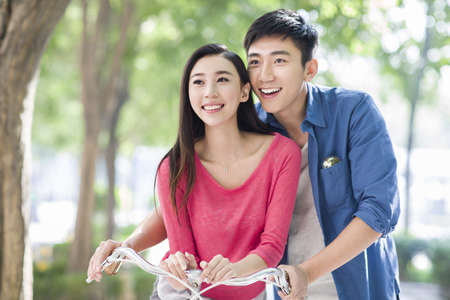 move in: Young couple riding bicycle at campus