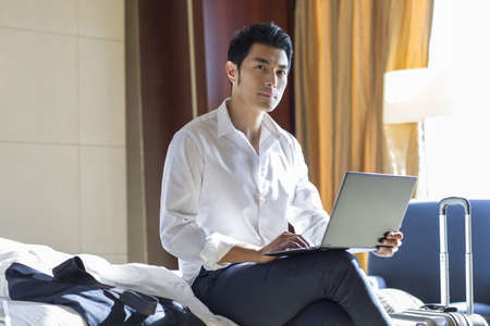 Young businessman using laptop in hotel room LANG_EVOIMAGES