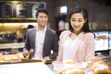drinks after work: Young couple choosing breads in bakery
