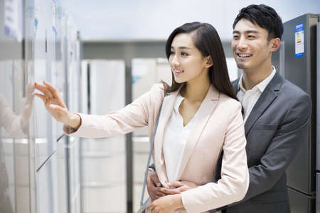 major household appliance: Young couple buying refrigerator in electronics store LANG_EVOIMAGES
