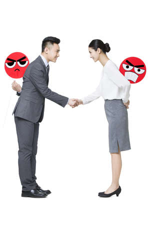 conflictos sociales: Business person shaking hands with angry emoticon faces behind their backs LANG_EVOIMAGES