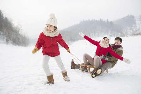 ski walking: Happy family playing with sled on the snow