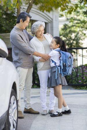 Little schoolgirl and her grandparents LANG_EVOIMAGES