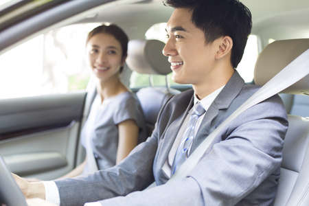 transportation: Young businessman driving car with his wife sitting next to him