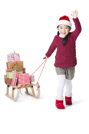 pull out: Happy girl pulling Christmas gifts on sled