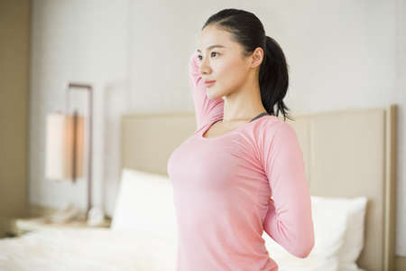 home life: Young woman stretching in bedroom LANG_EVOIMAGES