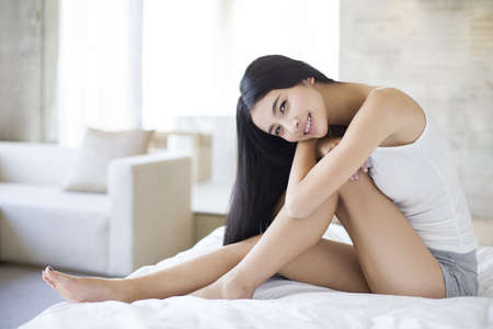 Portrait of beautiful young woman on bed