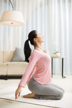 self care: Young woman practicing yoga in living room