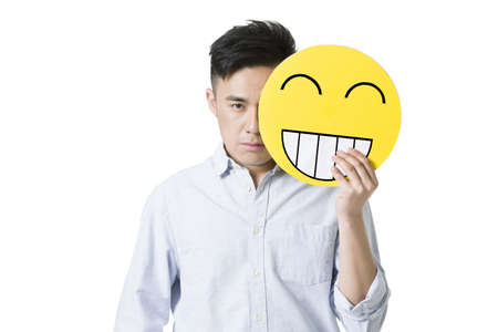 two faced: Young man holding a happy emoticon face