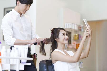 Female customer taking self portrait in barber shop