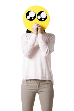 Young woman with a cute emoticon face in front of her face LANG_EVOIMAGES