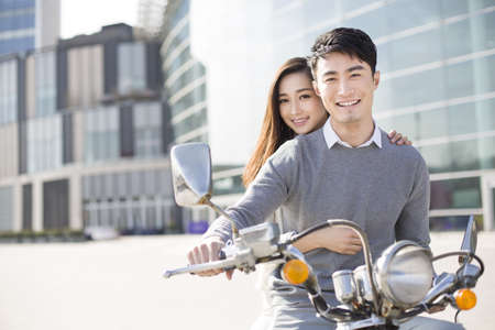transportation: Young couple riding motorcycle together