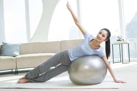 self conscious: Young woman practicing yoga with fitness ball