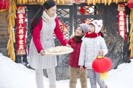 Happy mother and children with Chinese Dumplings