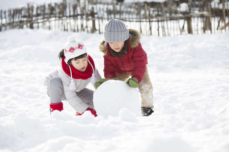 chainlink fence: Happy children rolling snowball together