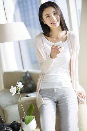 Happy young woman using smart phone