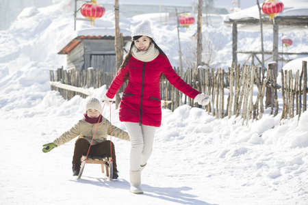 Young mother pulling son on sled LANG_EVOIMAGES