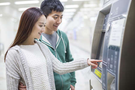 taking a wife: Young couple using ticket machine