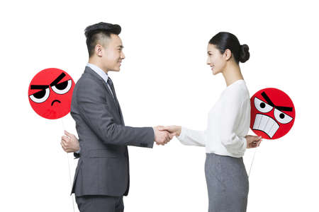 two faced: Business person shaking hands with angry emoticon faces behind their backs LANG_EVOIMAGES