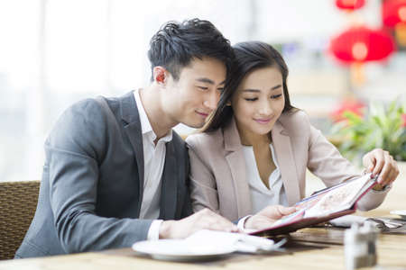drinks after work: Young couple reading menu in restaurant LANG_EVOIMAGES