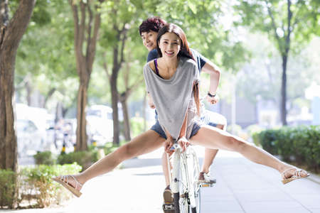 Young couple riding bicycle at campus