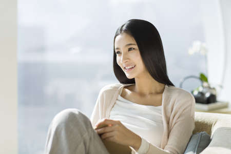 Happy young woman sitting on sofa with a book