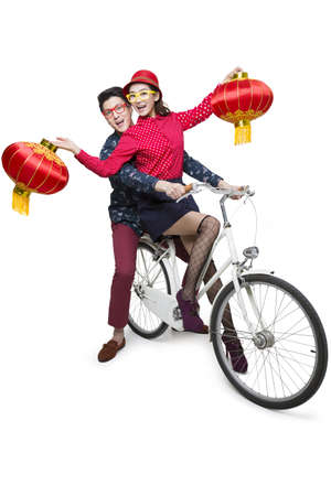 Young couple riding on a bike with Chinese lanterns