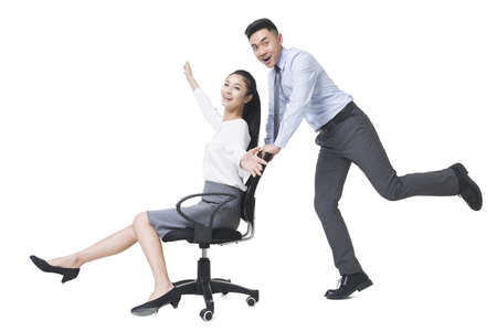 Businessman pushing businesswoman in rolling office chair