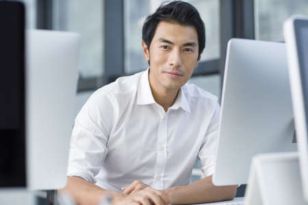 technology: Young businessman using computer in office