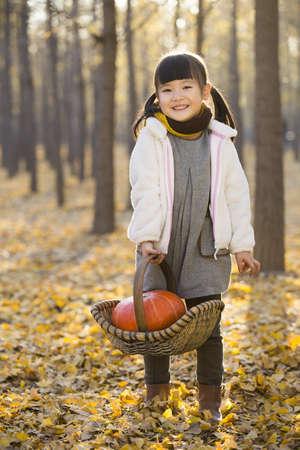 Little girl holding pumpkin in autumn woods