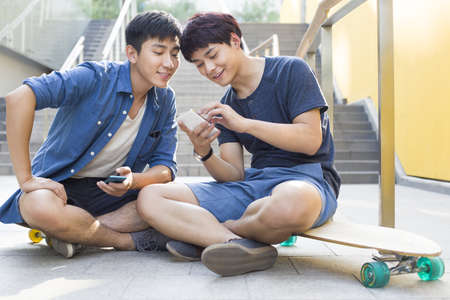 Young men sitting on skateboards looking at a smart phone