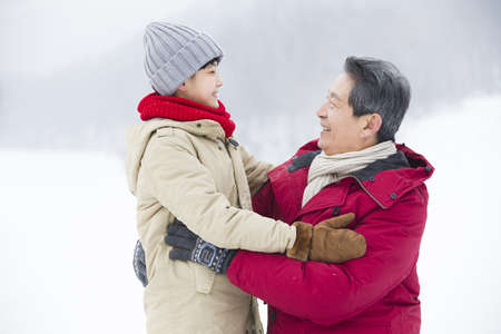 Happy grandfather and grandson embracing on the snow LANG_EVOIMAGES