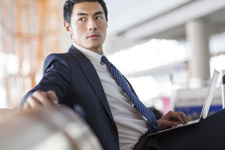 Young businessman using laptop in airport LANG_EVOIMAGES