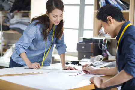 learning new skills: Two fashion designers working in studio