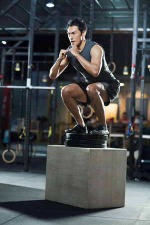 Young man doing box jump in crossfit gym LANG_EVOIMAGES