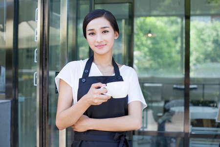 Shopkeeper standing in doorway of coffee shop