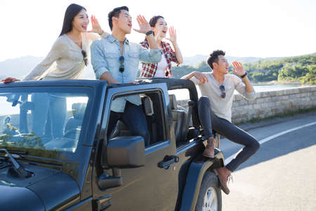 roadside stand: Chinese friends having fun in a jeep LANG_EVOIMAGES