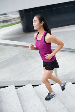 Young woman running up stairs for exercise