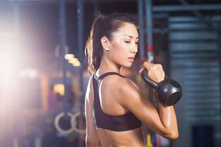 Young woman training with kettlebell in crossfit gym