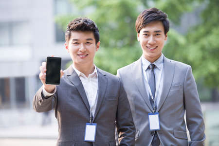 cardkey: Young business person showing smart phone