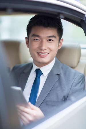 transportation: Businessman sitting in car back seat