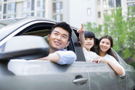 Happy young family in a car LANG_EVOIMAGES