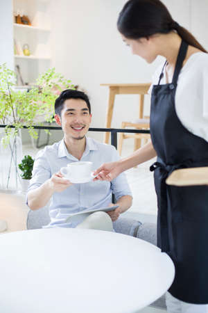 Waitress serving young man a cup of coffee