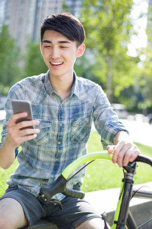 road cycling: Happy young man using smart phone
