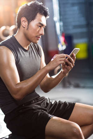 Young man using smart phone in gym LANG_EVOIMAGES