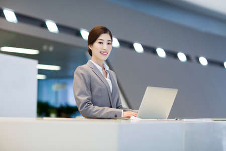 looking for job: Confident receptionist using laptop at reception counter LANG_EVOIMAGES