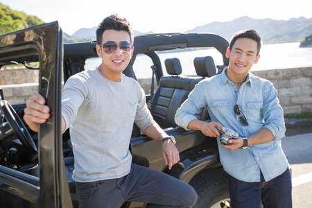 close range: Happy young Chinese men and jeep