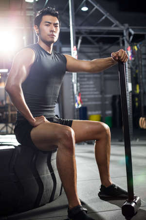Young man sitting on tire in gym LANG_EVOIMAGES