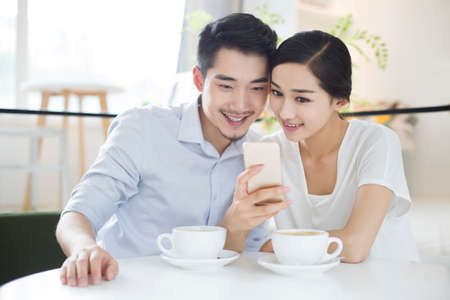 food drink industry: Happy young couple using smart phone in coffee shop