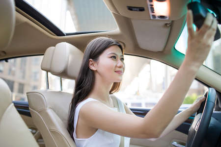 Young woman driving car LANG_EVOIMAGES
